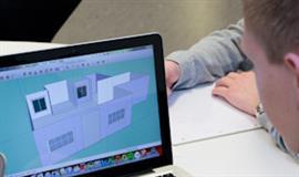 Billed af en dreng der arbejder på en computer